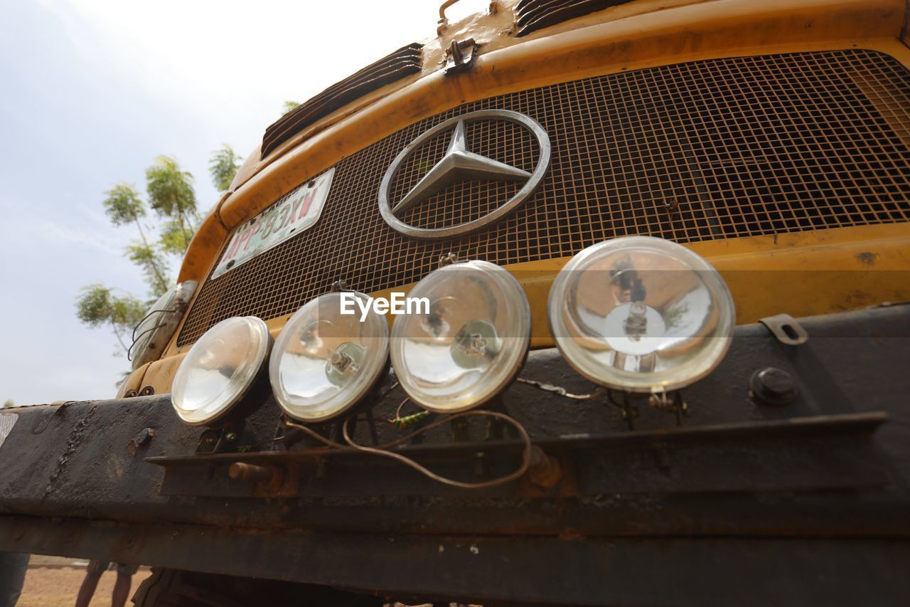 mode of transportation, no people, land vehicle, retro styled, transportation, day, metal, sky, close-up, outdoors, headlight, car, low angle view, old, nature, motor vehicle, vintage car, wood - material, still life