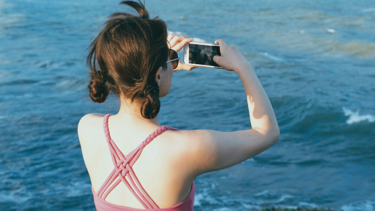 Rear View Of Mid Adult Woman Photographing Sea