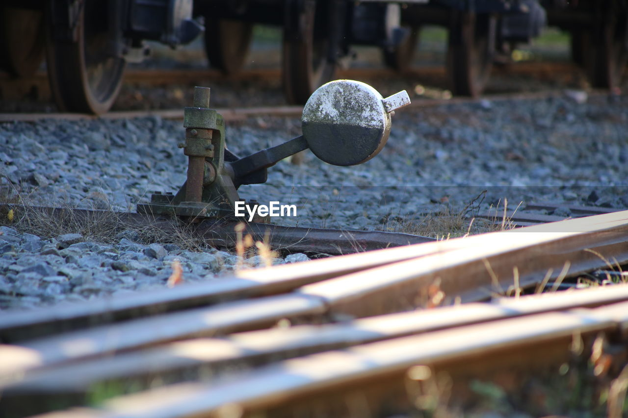 selective focus, metal, day, no people, close-up, nature, outdoors, track, railroad track, rail transportation, industry, wood - material, transportation, mode of transportation, solid, water, work tool, wheel