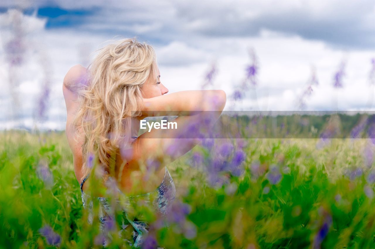 Woman with hand in hair standing on flowering plants on field