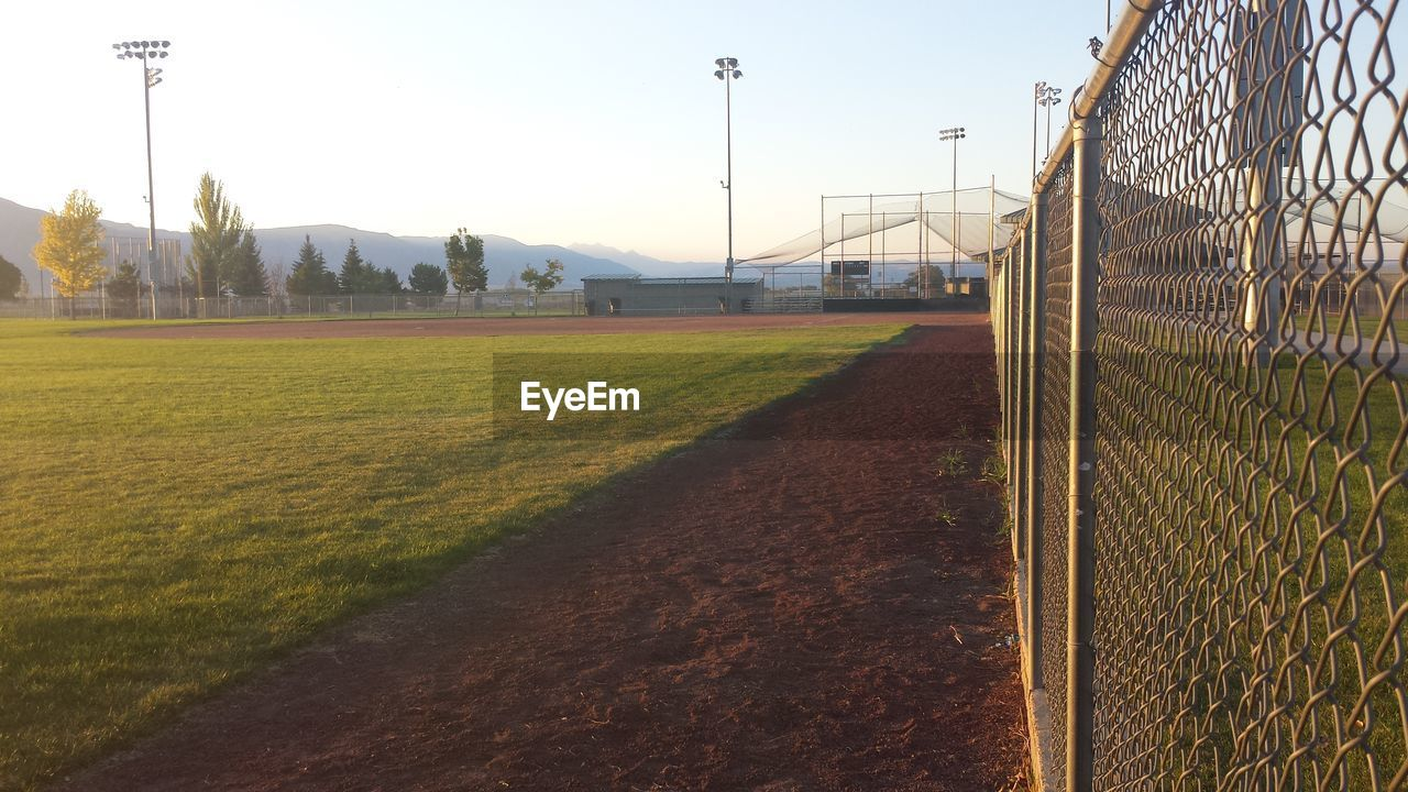 grass, sky, plant, fence, nature, sport, boundary, field, barrier, day, land, playing field, no people, landscape, soccer, green color, sunlight, growth, team sport, safety, outdoors