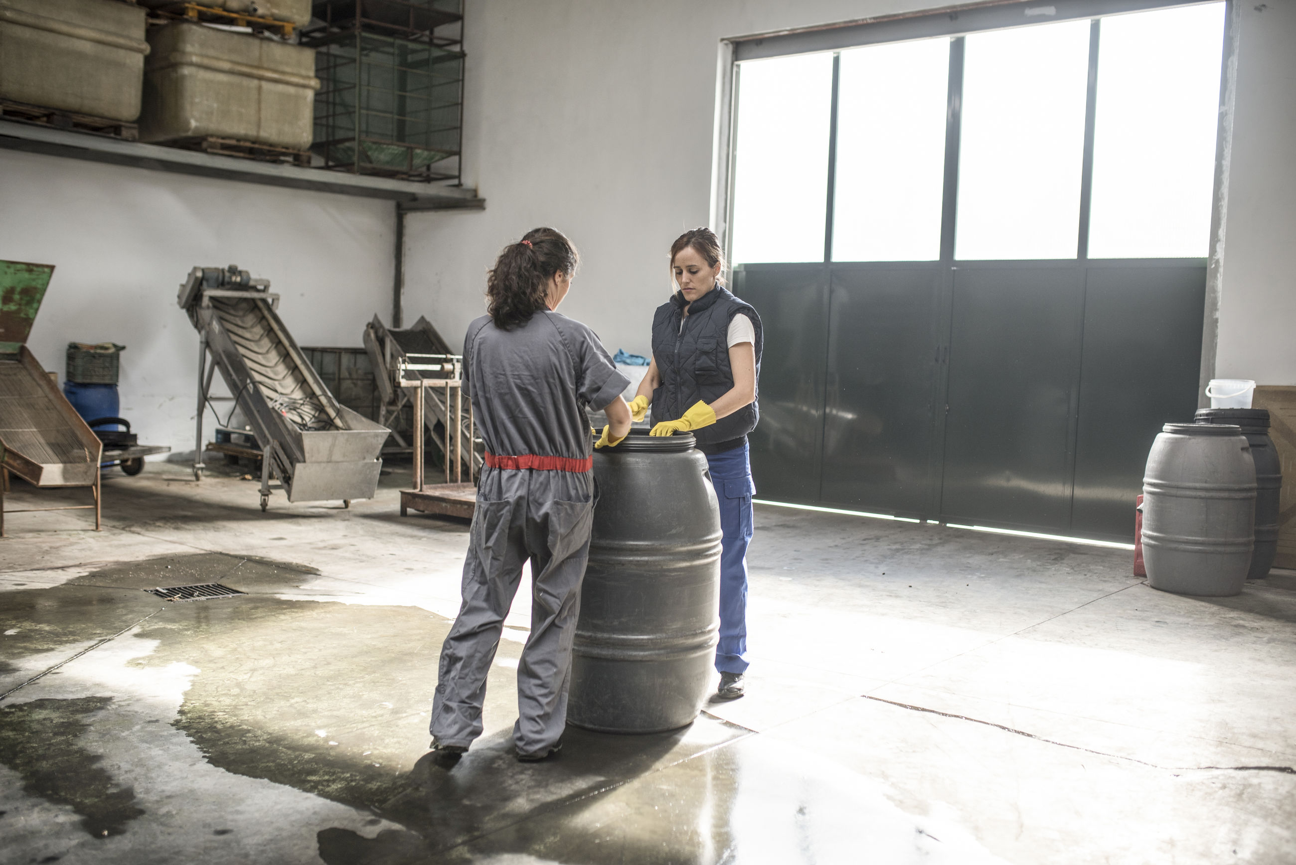 Female workers with drum in workshop