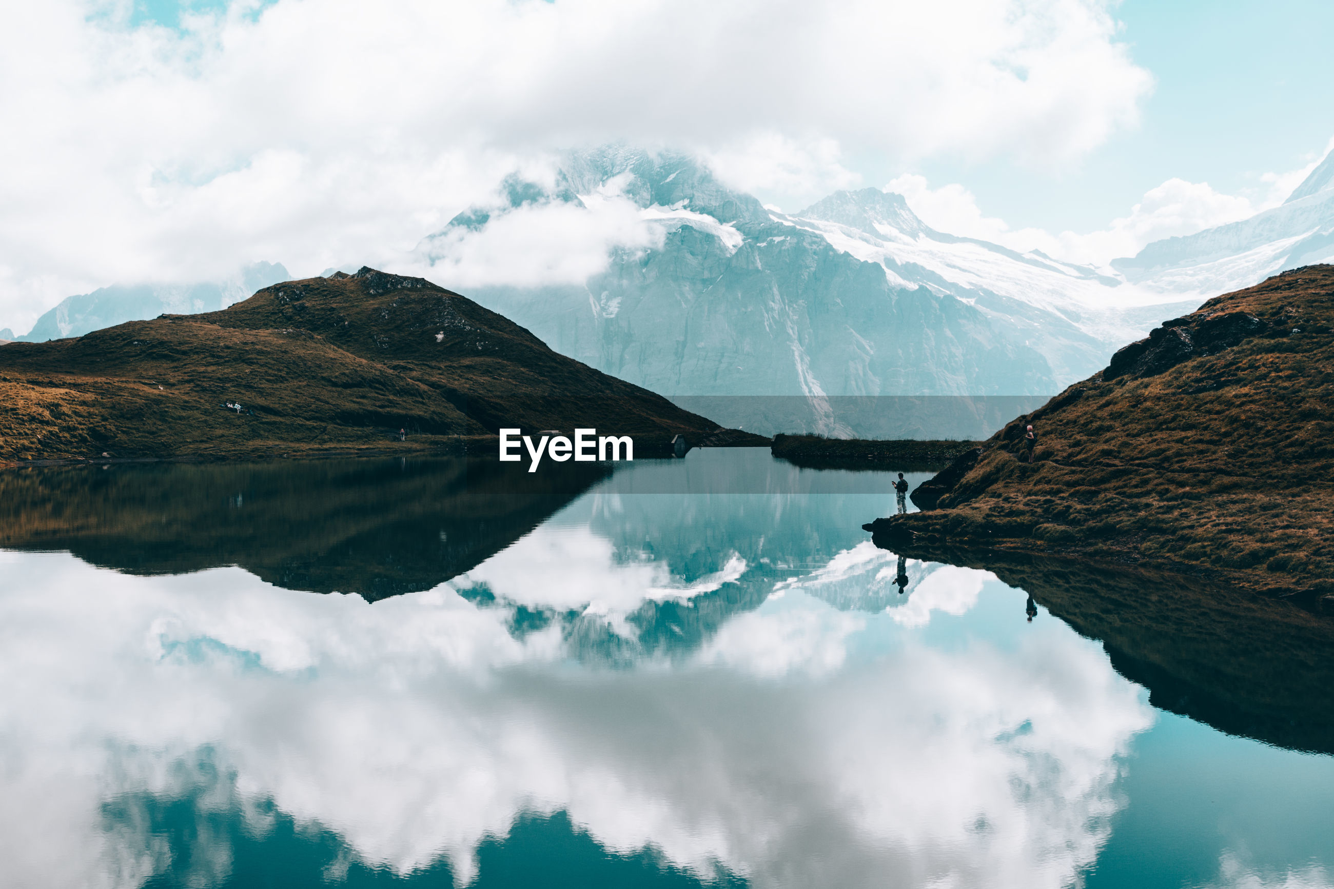 Panoramic view of calm lake surrounded by mountains against cloudy sky