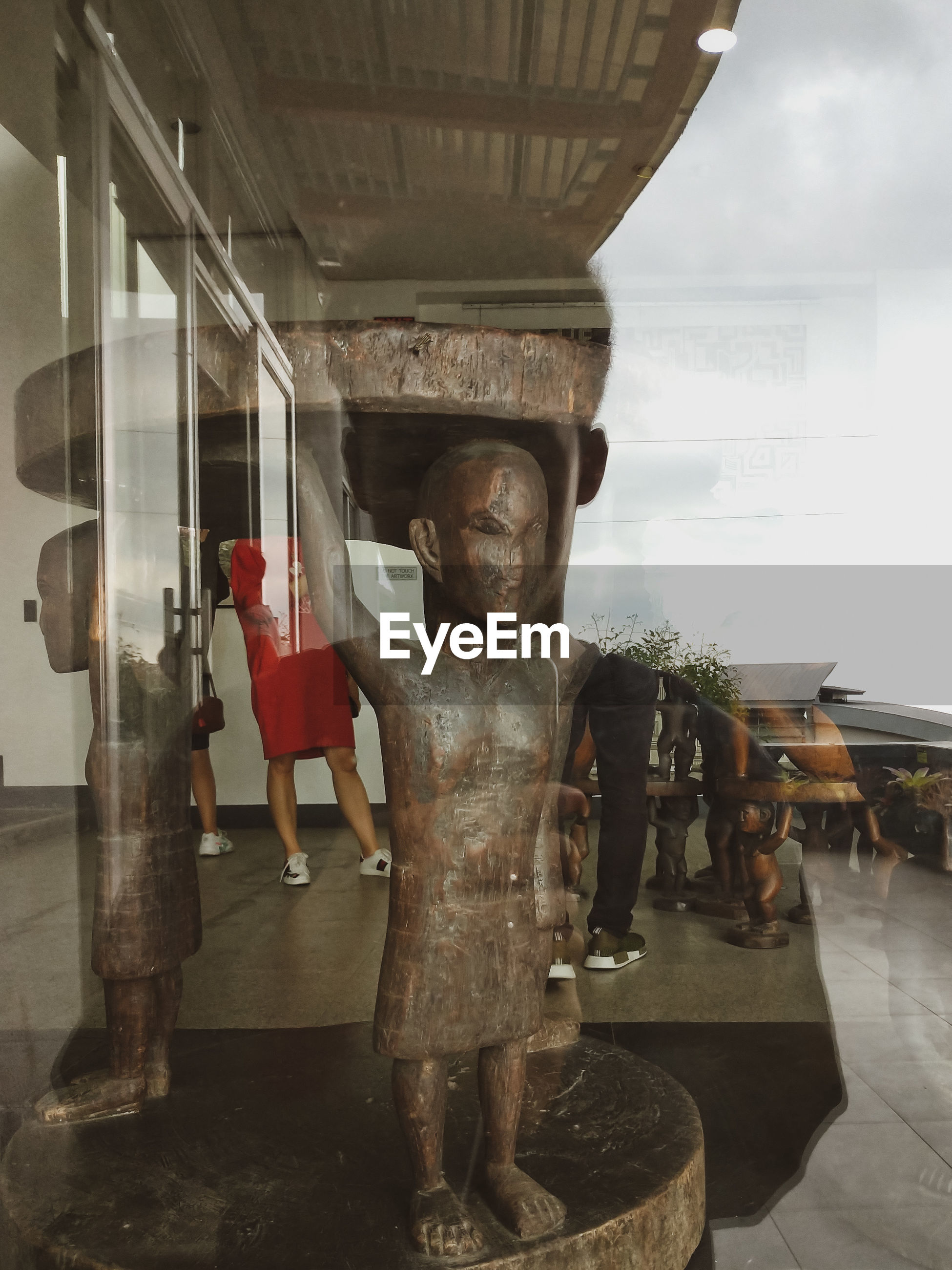 DIGITAL COMPOSITE IMAGE OF STATUE AND WOMAN IN GLASS