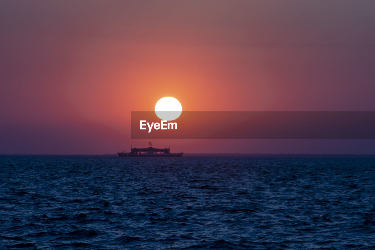 water, sunset, sea, sky, beauty in nature, sun, horizon over water, scenics - nature, horizon, waterfront, tranquil scene, tranquility, orange color, idyllic, non-urban scene, nautical vessel, no people, nature, rippled, outdoors, eclipse