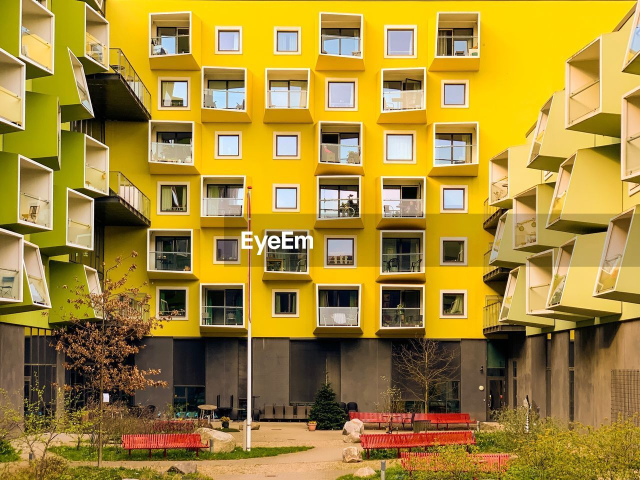 architecture, building exterior, built structure, building, residential district, yellow, city, window, no people, apartment, day, plant, outdoors, nature, house, sunlight, motor vehicle, grass, mode of transportation, footpath, housing development
