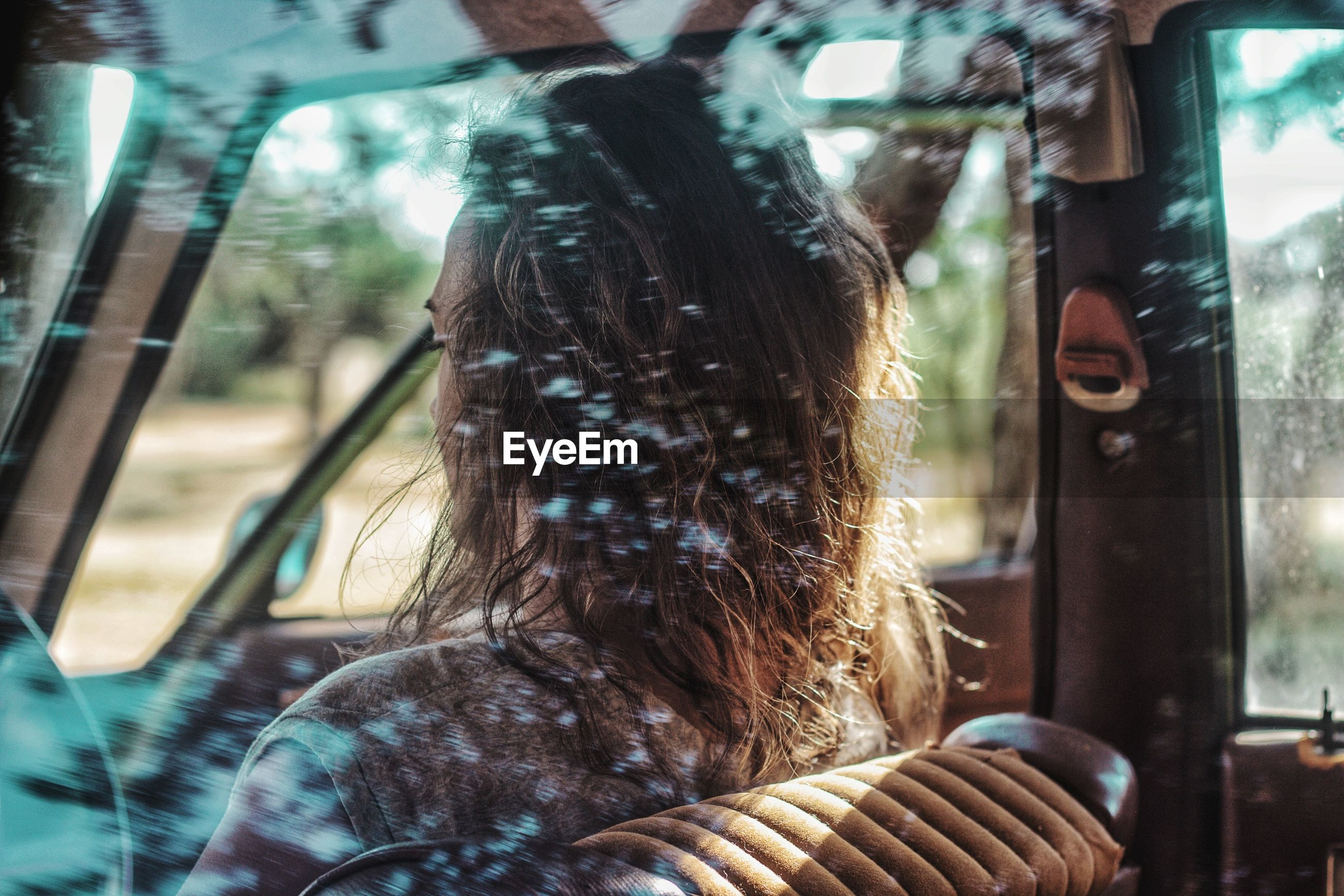Woman sitting in car seen through window