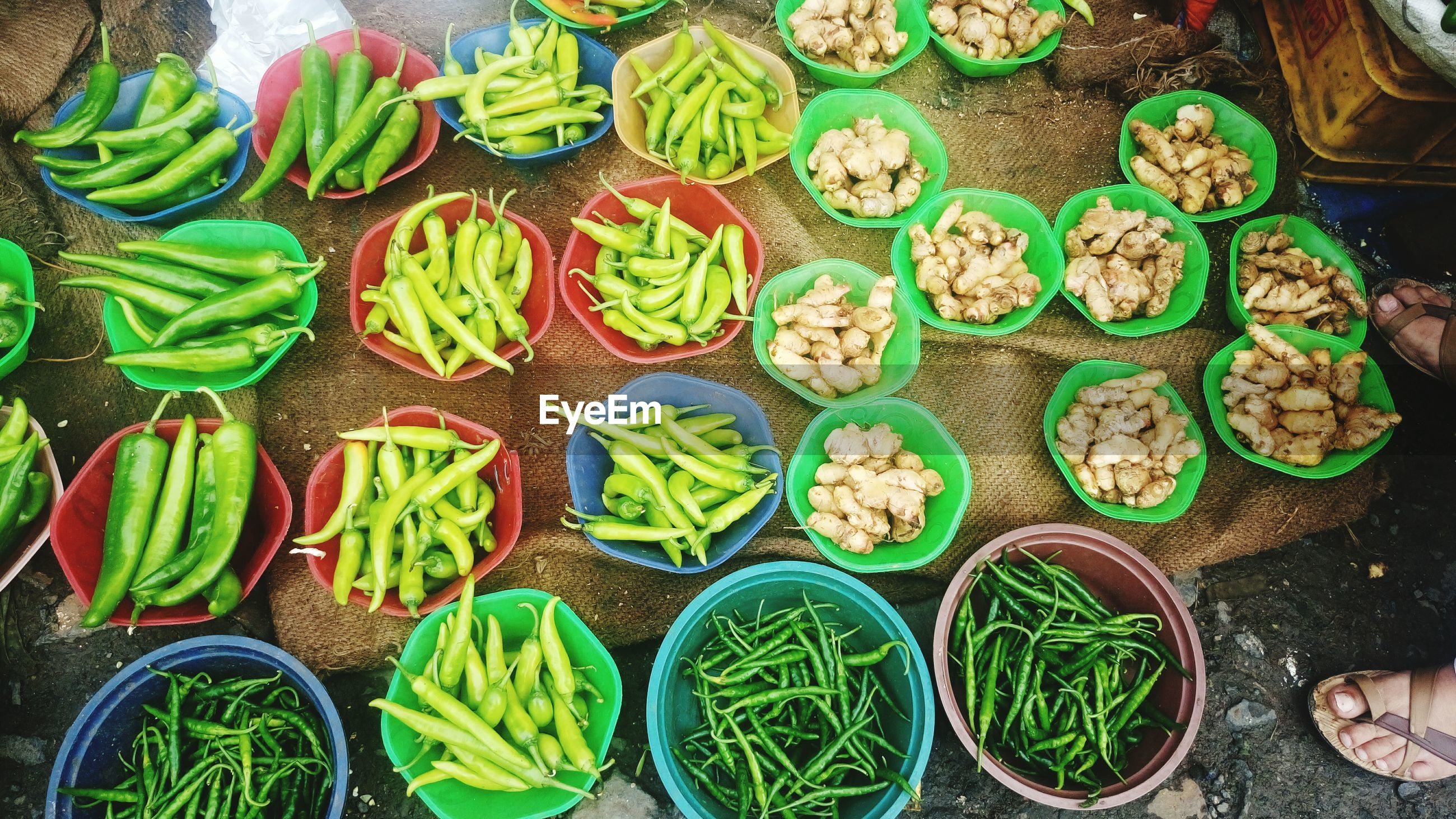 High angle view of green chili peppers and garlic in containers at market for sale
