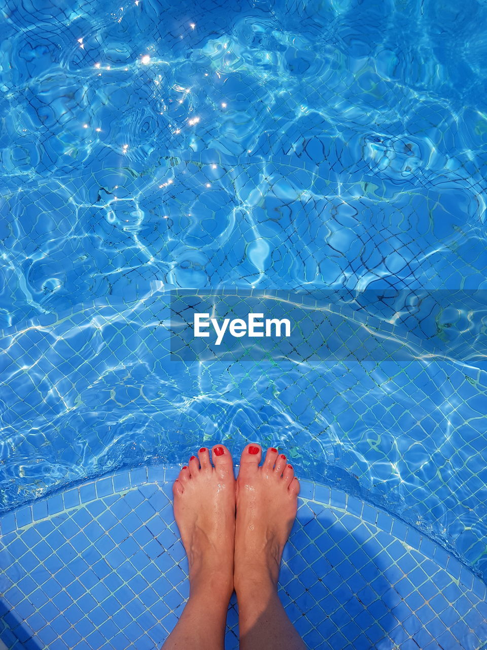 Low section of woman relaxing at poolside