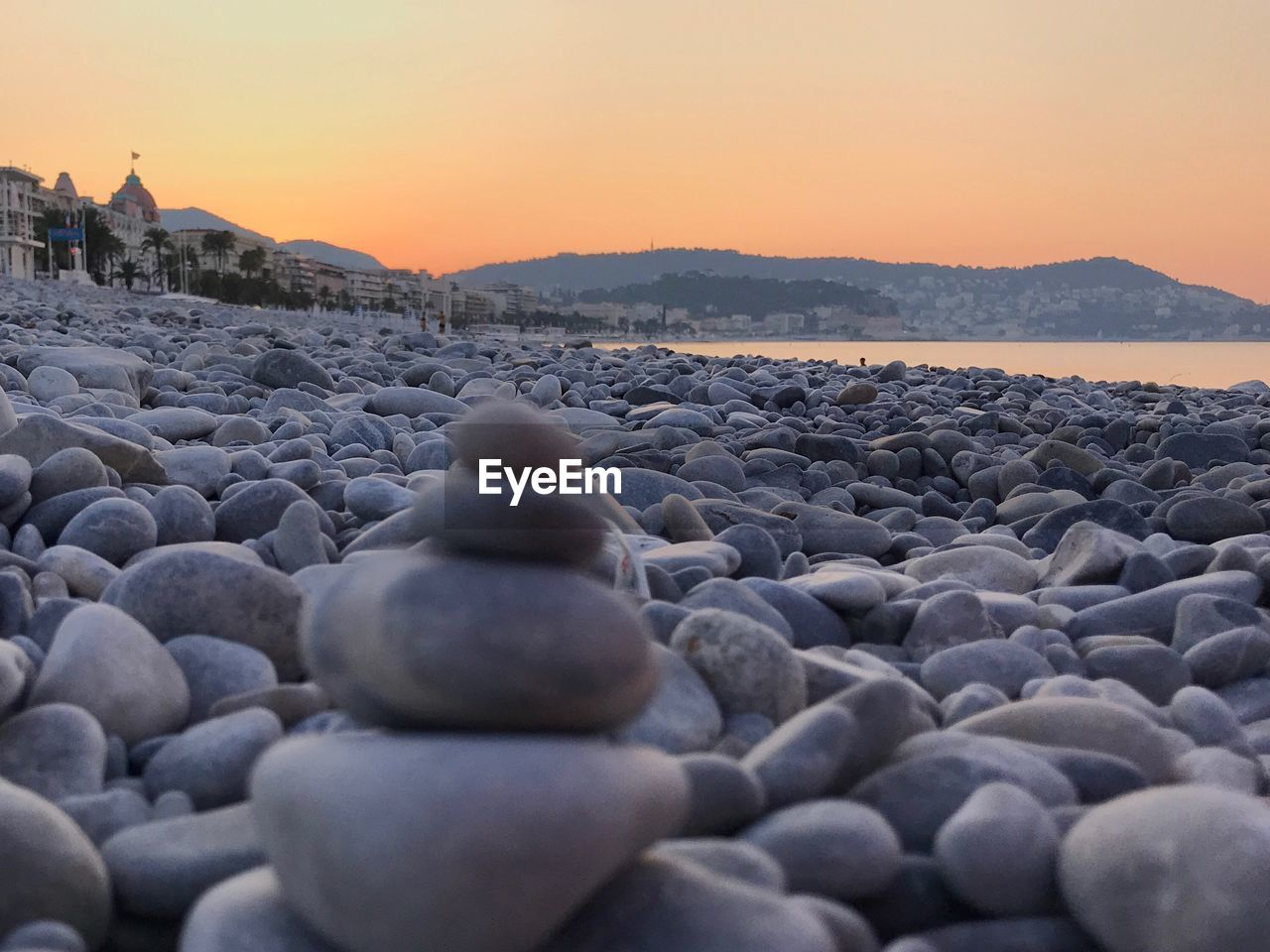 sunset, sky, rock, beach, stone, pebble, solid, land, stone - object, tranquil scene, nature, tranquility, zen-like, beauty in nature, scenics - nature, water, rock - object, sea, stack, balance, no people, outdoors, surface level