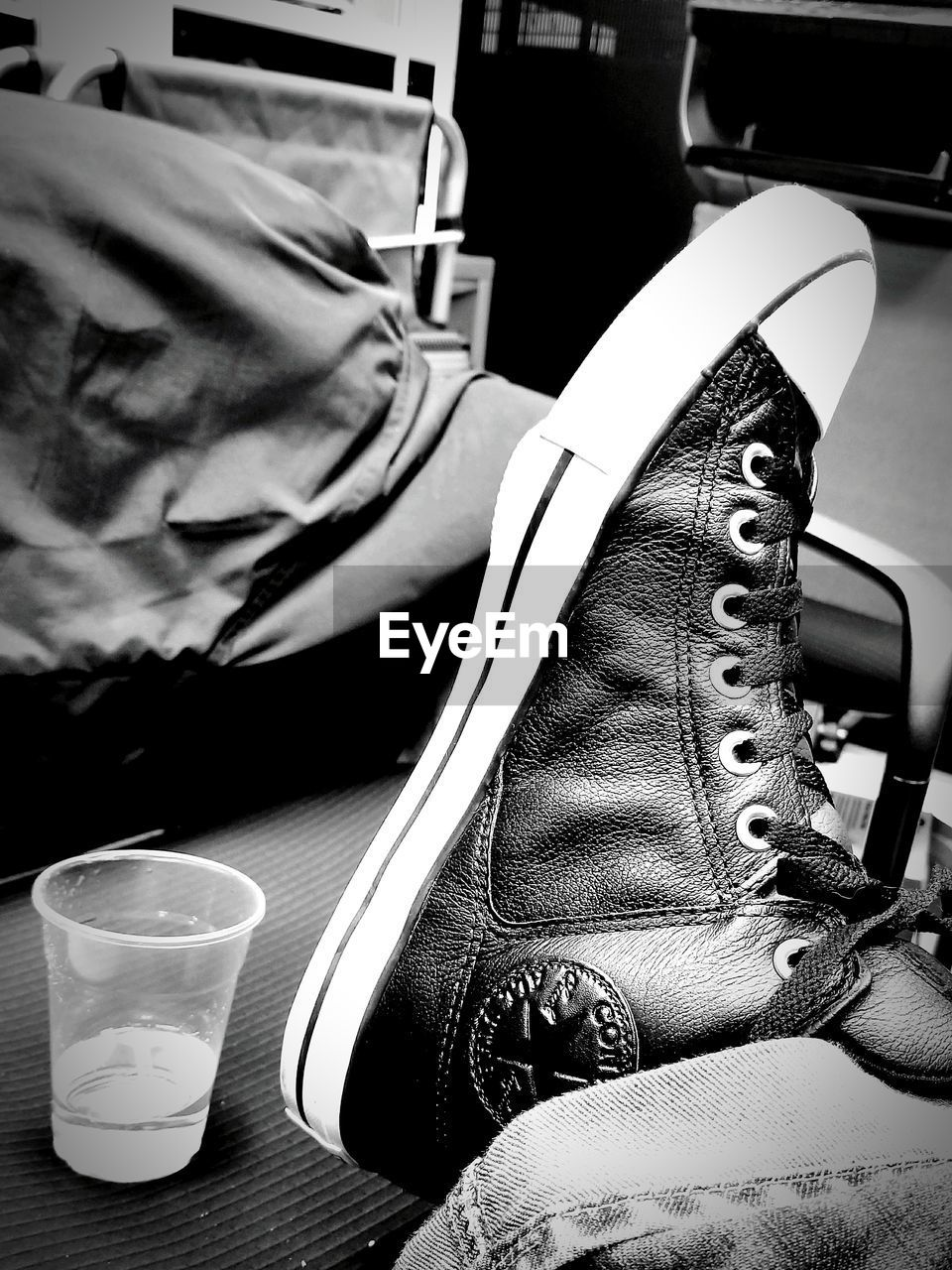 shoe, indoors, real people, close-up, table, focus on foreground, still life, drink, refreshment, fashion, relaxation, furniture, lifestyles, low section, food and drink, bed, glass, jeans
