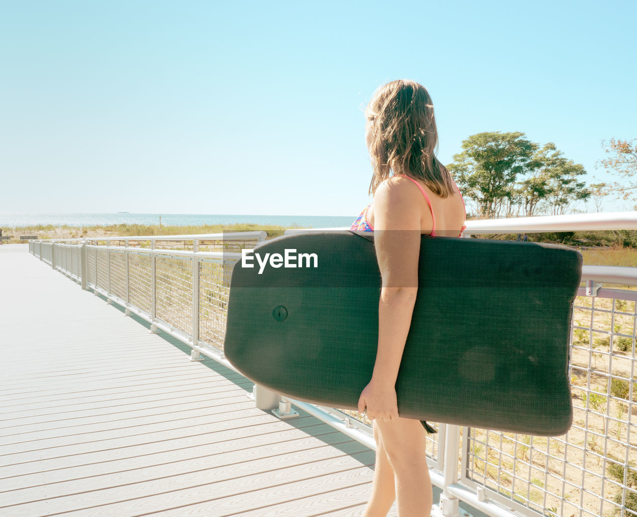 Side View Of Girl Holding Board While Standing On Footpath Against Clear Sky During Sunny Day