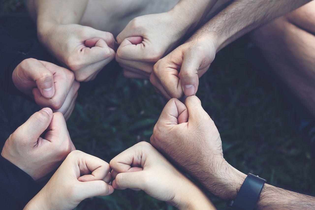Cropped image of friends huddling fists outdoors