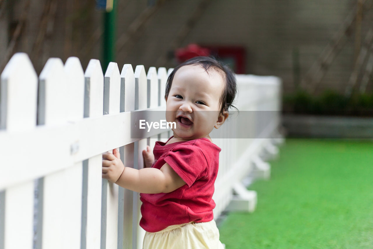 Portrait of cute girl smiling by fence
