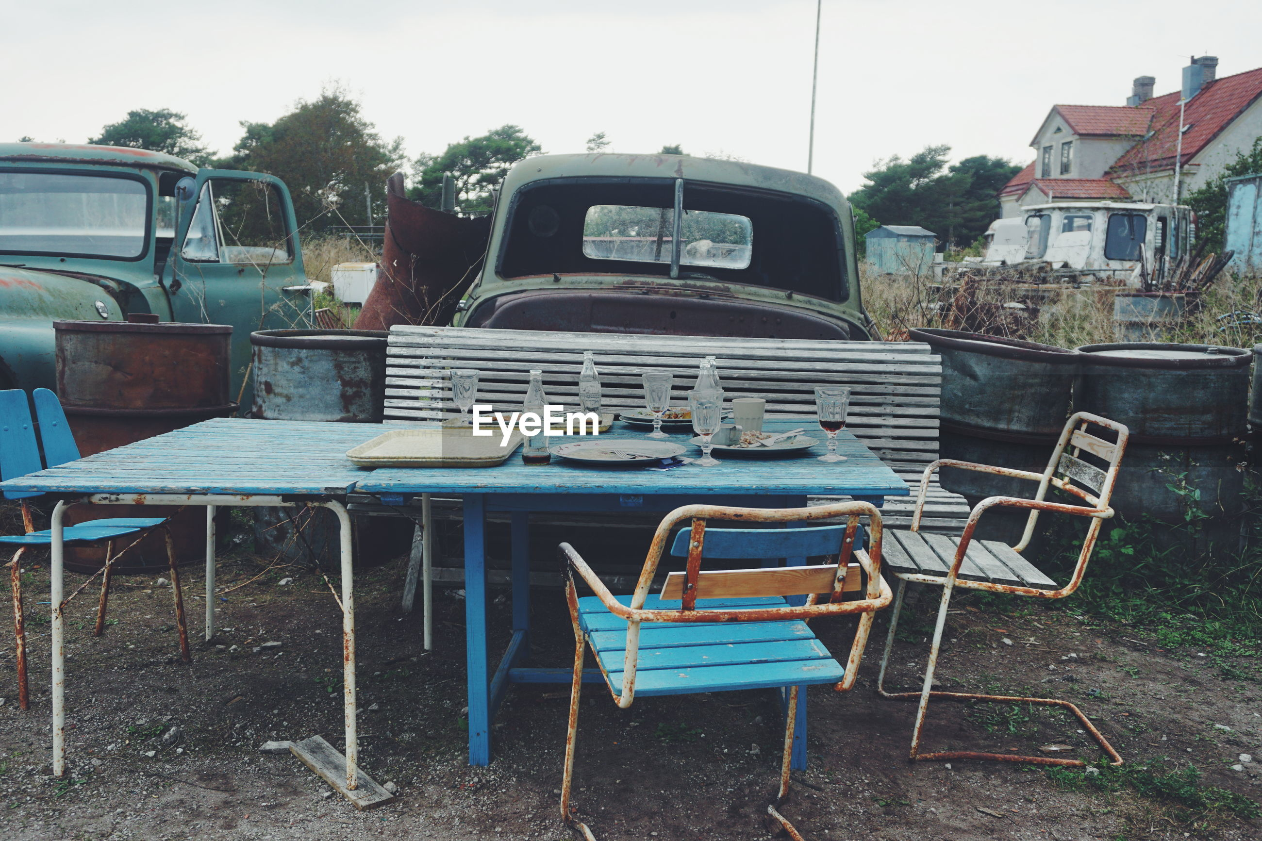 Tables and chairs against abandoned cars