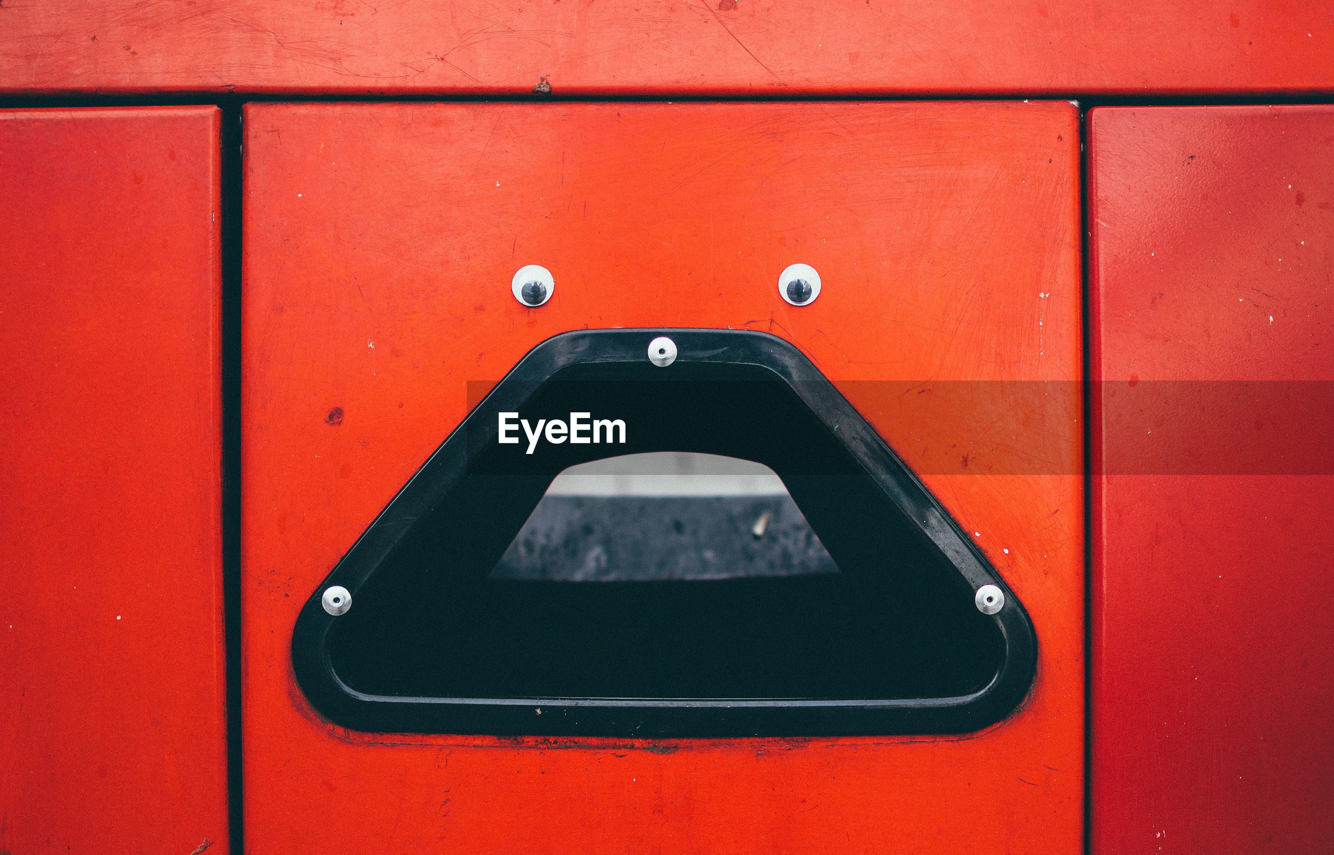 Anthropomorphic face on red trash can
