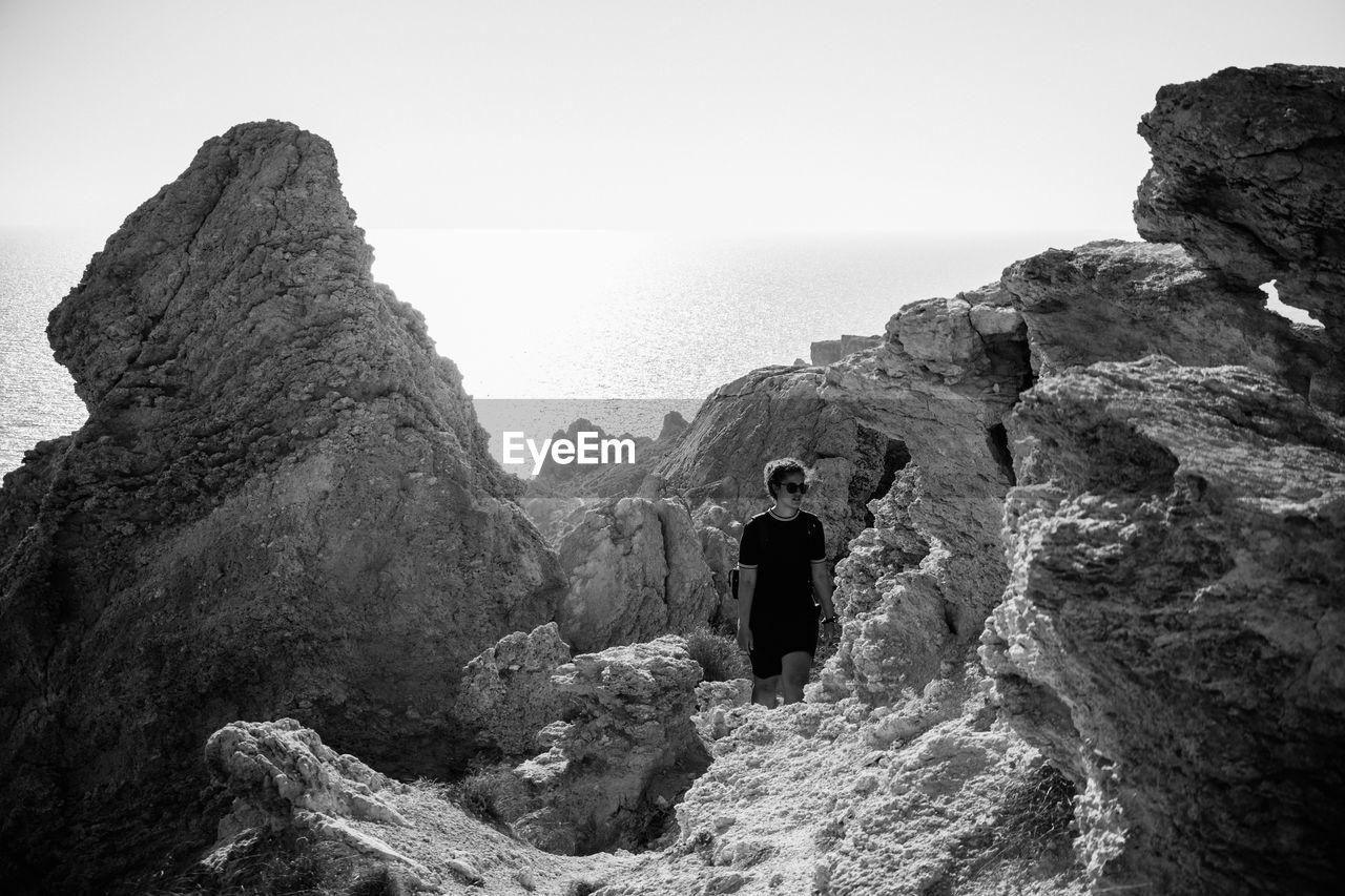 Woman Walking On Rocky Beach