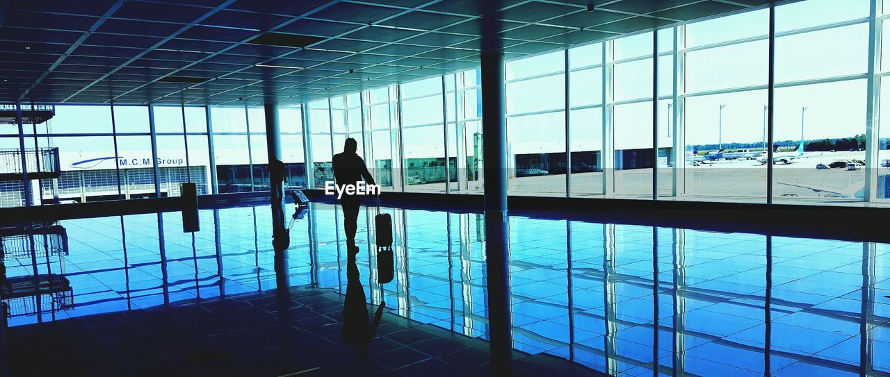 glass - material, real people, transparent, indoors, reflection, flooring, built structure, window, architecture, silhouette, people, airport, modern, tile, day, travel, men, adult, leisure activity, tiled floor, ceiling