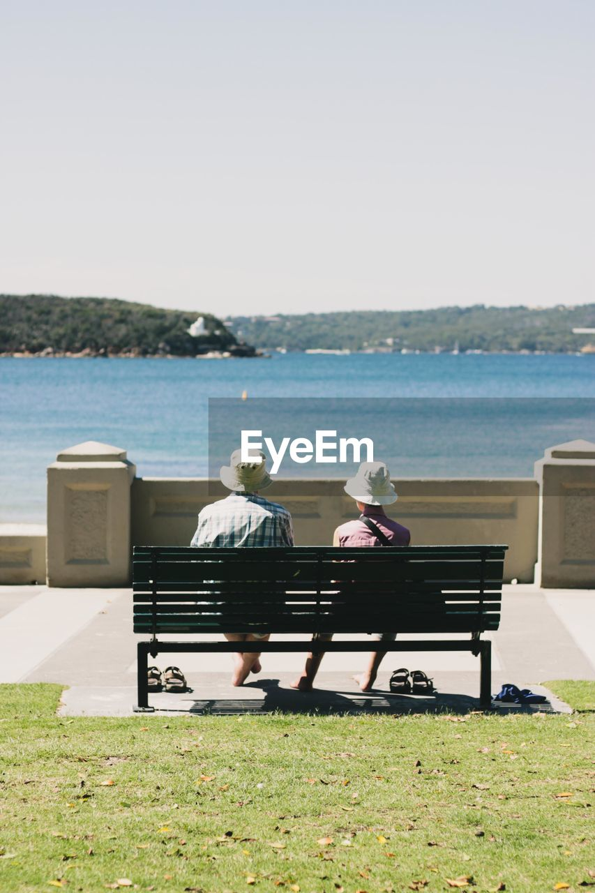 rear view, water, sea, sky, nature, sitting, bench, men, seat, two people, couple - relationship, women, adult, leisure activity, full length, clear sky, relaxation, lifestyles, land, outdoors, horizon over water, looking at view