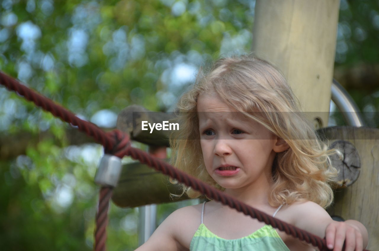 Scared Girl Holding Rope In Park