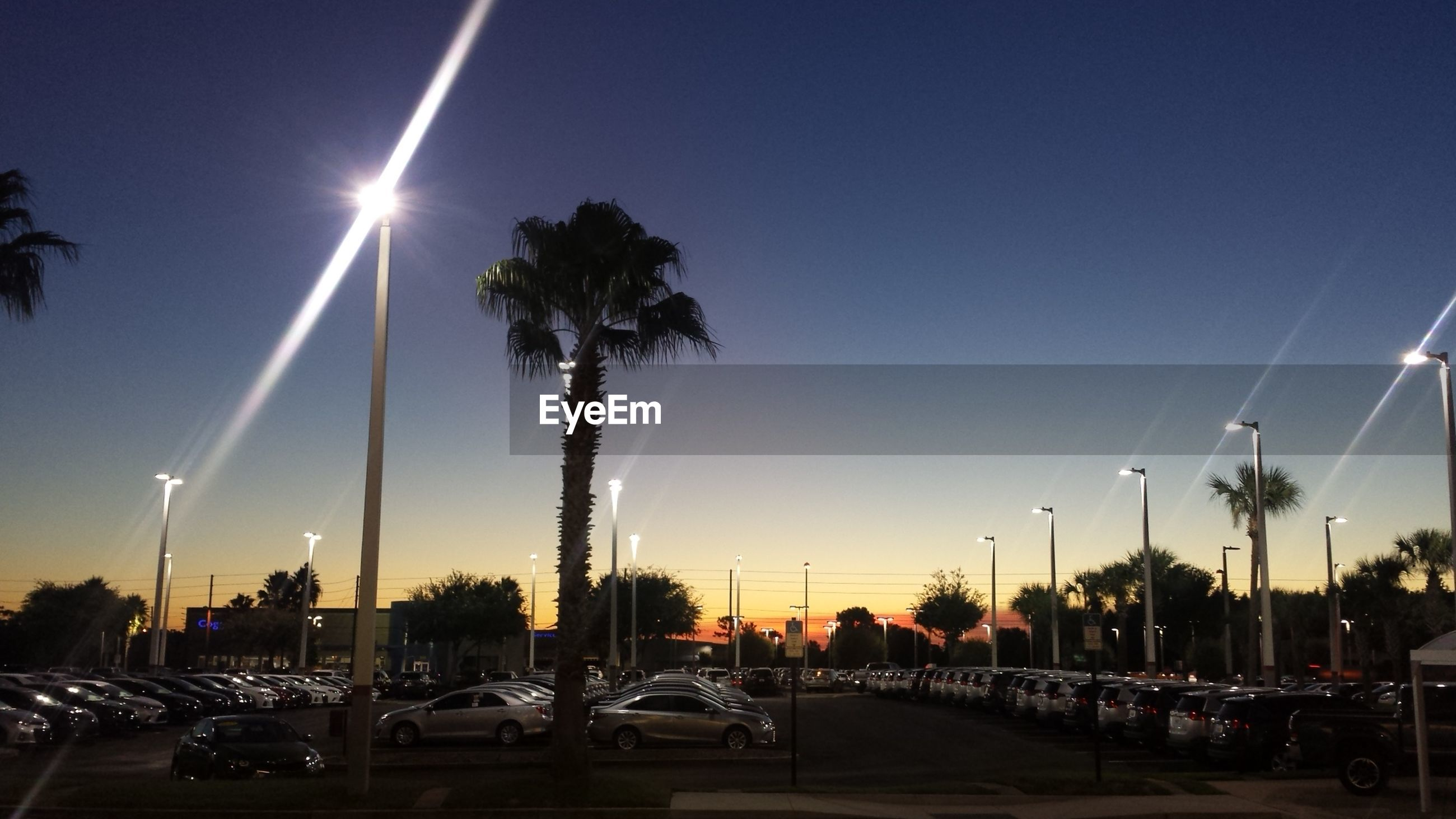 Cars in illuminated parking lot against sky during sunset
