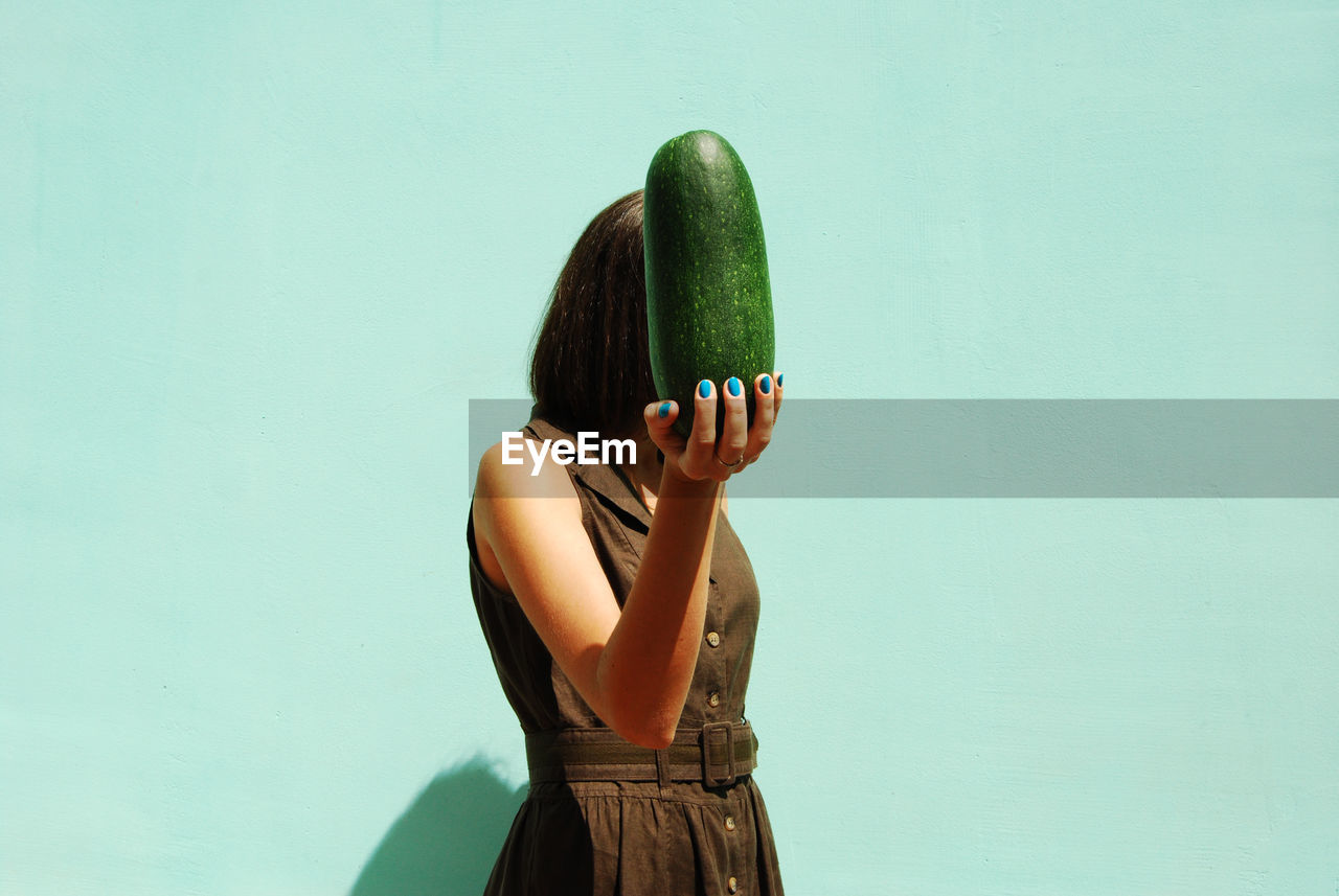 View of woman holding vegetable against wall