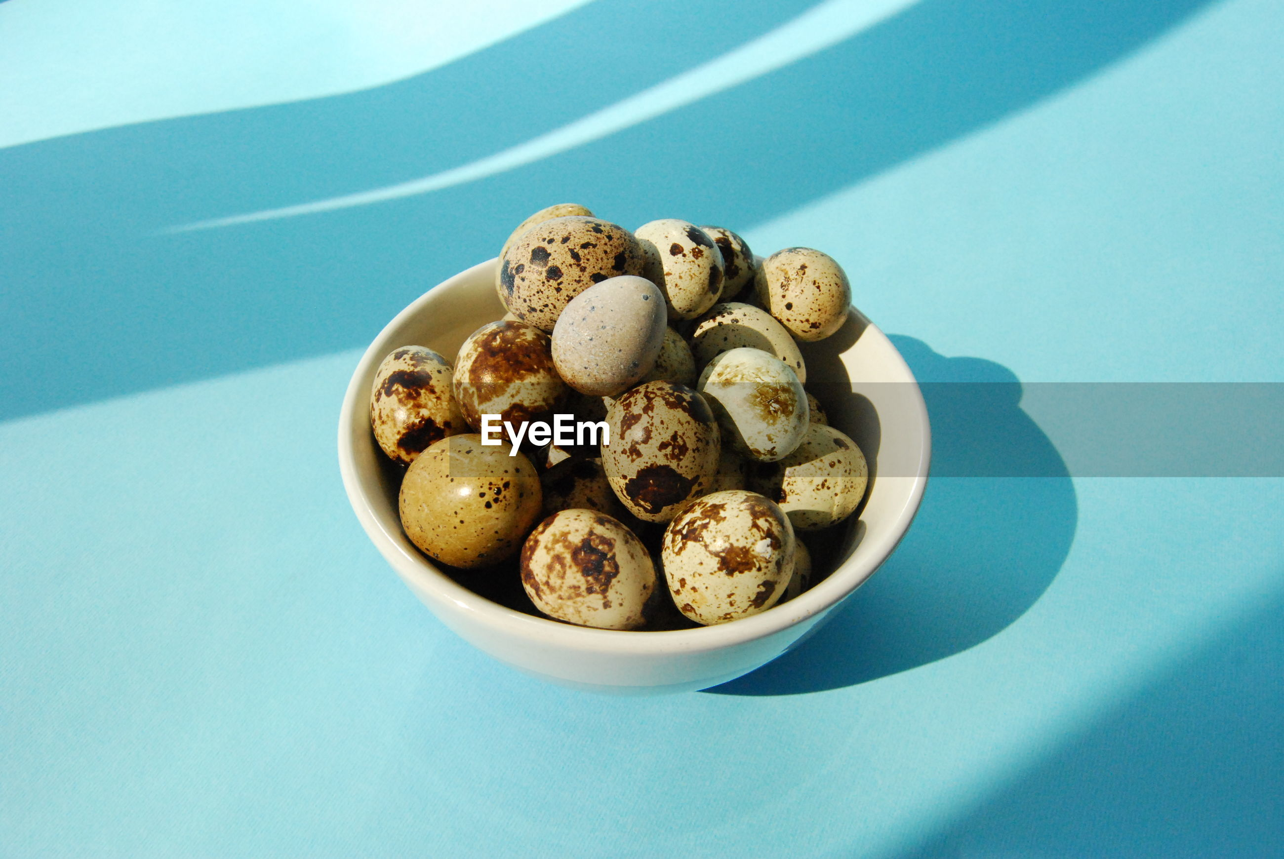 Eggs in bowl over blue background