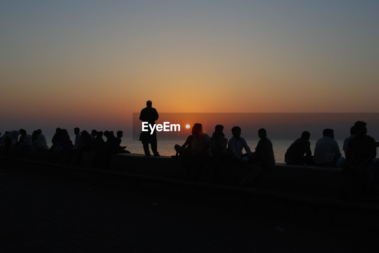 Silhouette people overlooking sea at sunset