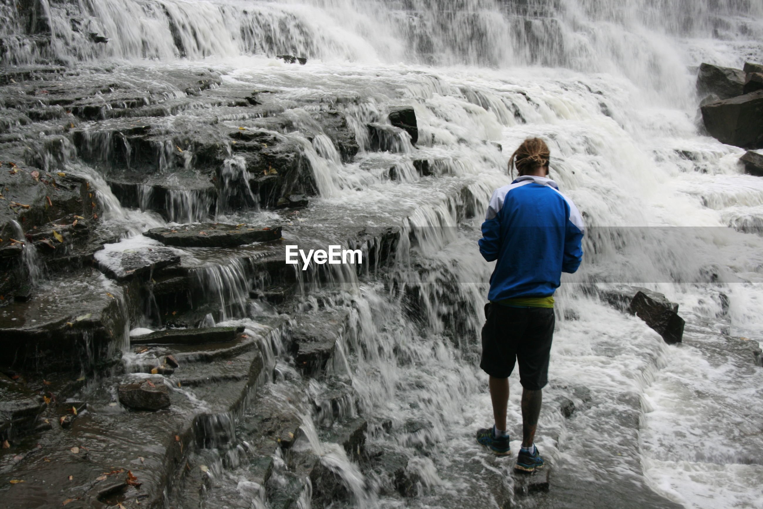 Full length rear view of man standing at waterfall