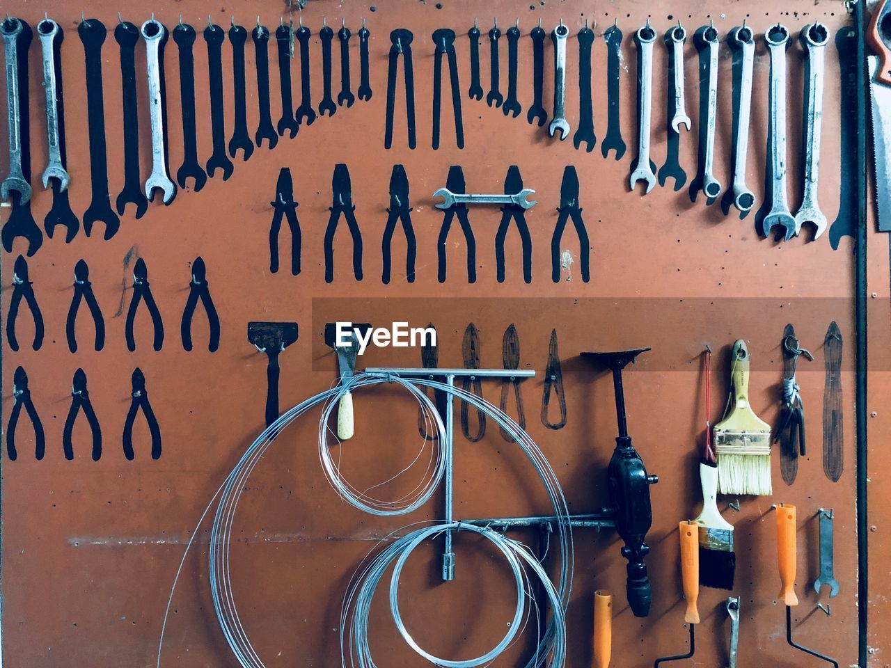 wall - building feature, metal, large group of objects, no people, indoors, hand tool, choice, work tool, tool, variation, order, arrangement, workshop, in a row, side by side, orange color, day, equipment, still life, spanner, garage