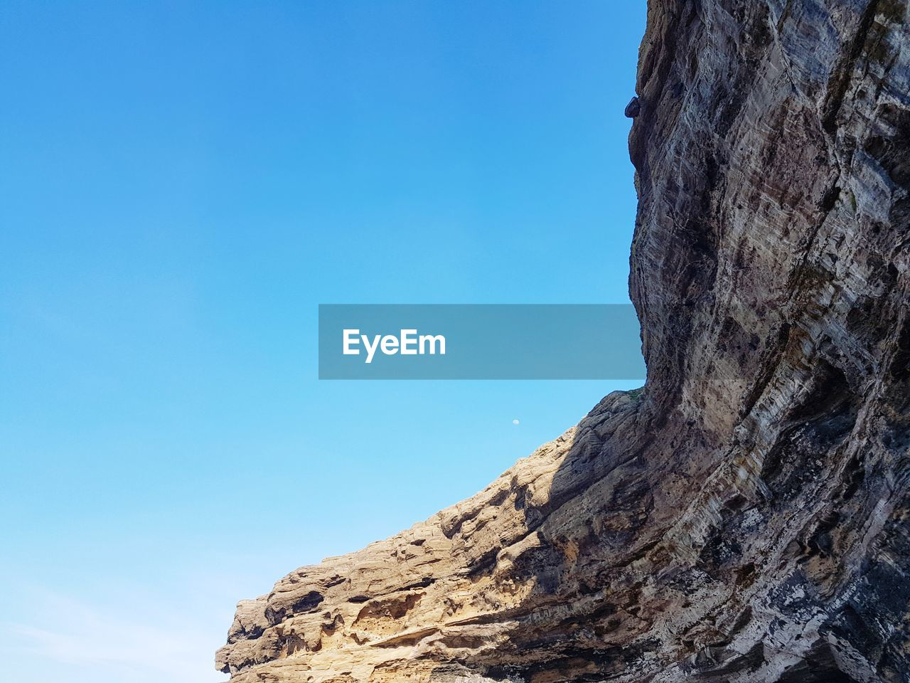 sky, blue, rock, nature, rock formation, low angle view, rock - object, tranquility, mountain, solid, beauty in nature, day, scenics - nature, no people, tranquil scene, copy space, clear sky, non-urban scene, physical geography, outdoors, formation, bark, eroded, mountain peak, arid climate