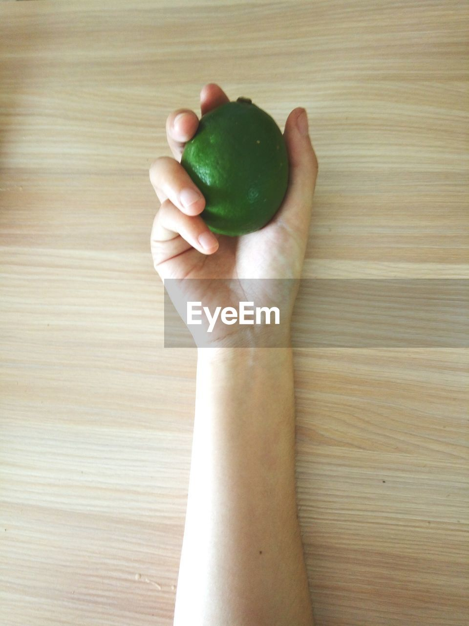Cropped Image Of Hand Holding Lemon On Wooden Table