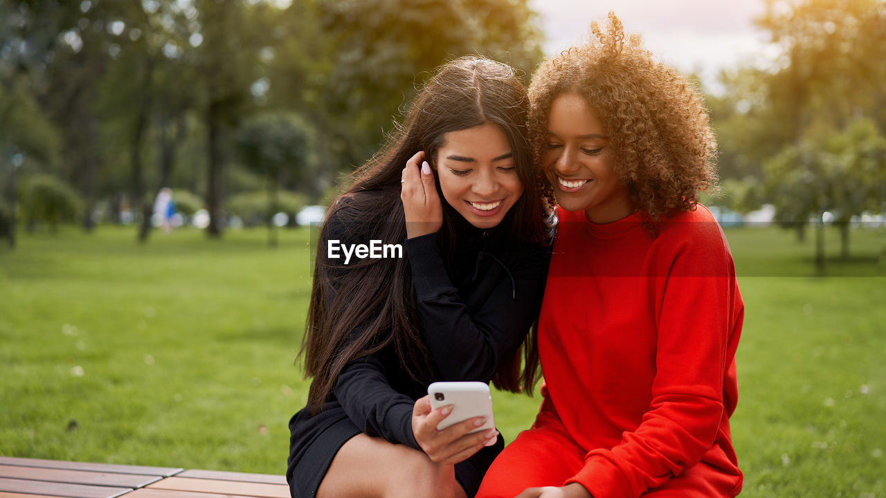 PORTRAIT OF A SMILING YOUNG WOMAN USING PHONE WHILE SITTING ON SMART