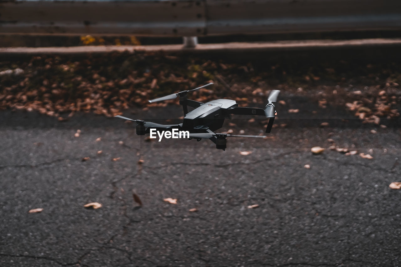transportation, no people, mode of transportation, day, nature, leaf, plant part, air vehicle, autumn, airplane, dry, selective focus, outdoors, land, focus on foreground, flying, stationary, field, road, seat, leaves