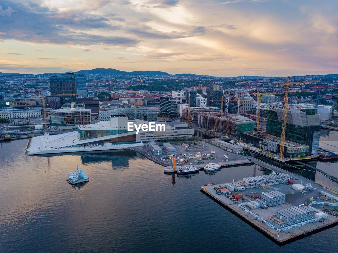 building exterior, architecture, sky, city, water, built structure, cityscape, cloud - sky, nautical vessel, sunset, transportation, high angle view, nature, no people, harbor, river, building, mode of transportation, waterfront, outdoors, office building exterior, skyscraper