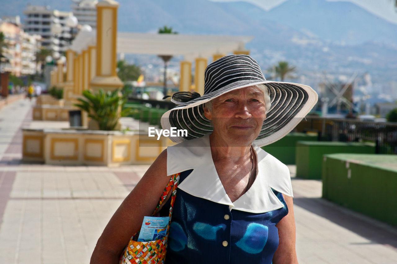 Portrait Of Smiling Senior Woman Wearing Sun Hat