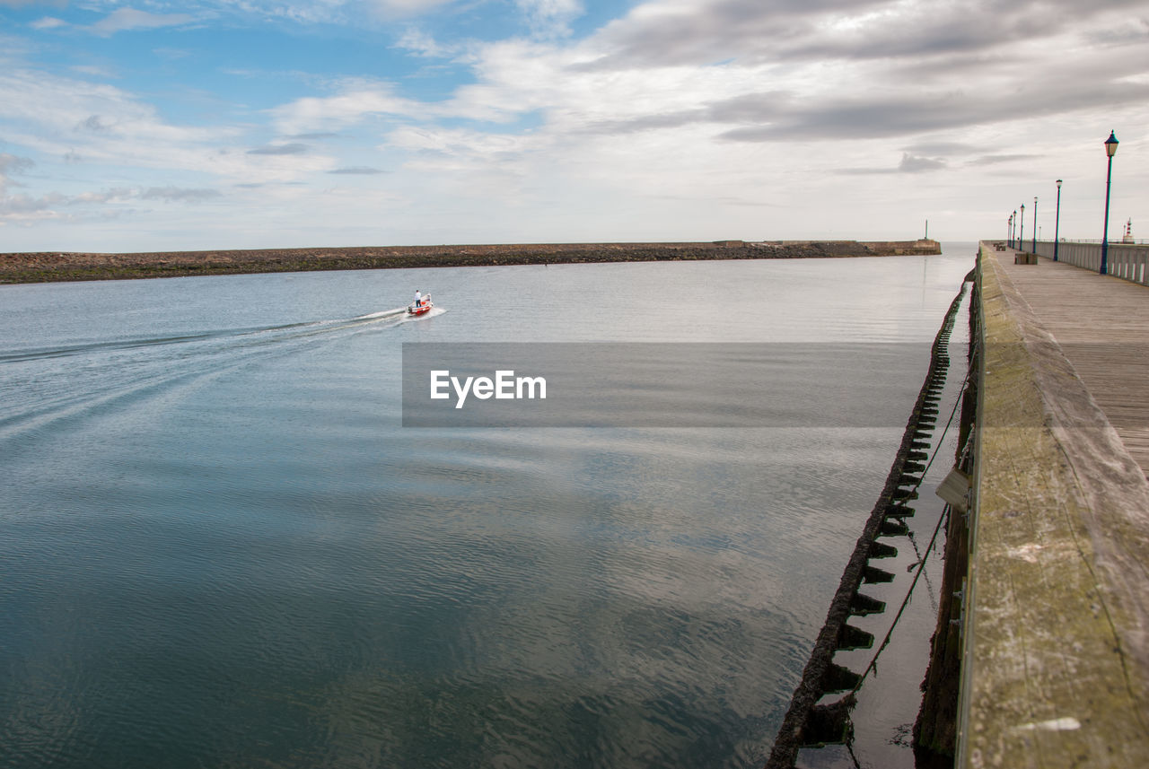 A small red fishing boat passes a pier on a calm day.