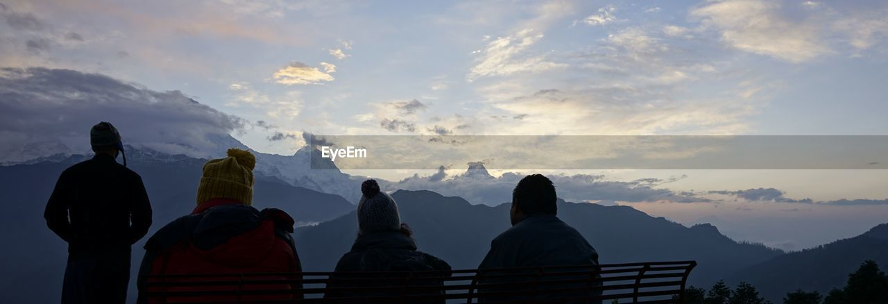Rear view of people at observation point against sky during sunset