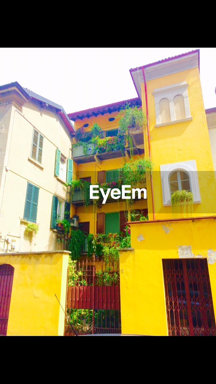 architecture, built structure, building exterior, yellow, window, house, no people, low angle view, residential building, outdoors, balcony, day, facade, sky, awning, window box