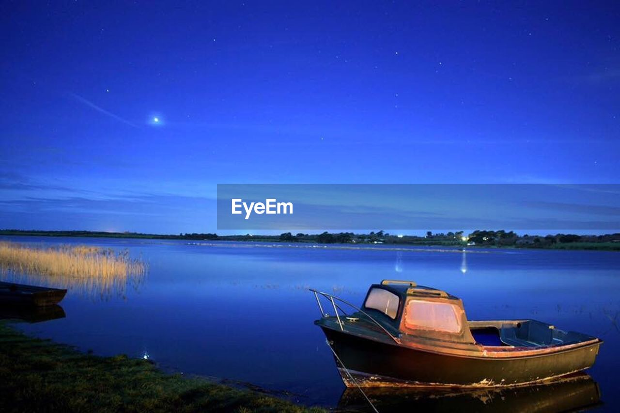 nautical vessel, water, night, star - space, moored, nature, lake, scenics, reflection, beauty in nature, tranquil scene, transportation, sky, no people, rowboat, tranquility, moon, mode of transport, outdoors, blue, clear sky, constellation, astronomy, galaxy, astrology sign