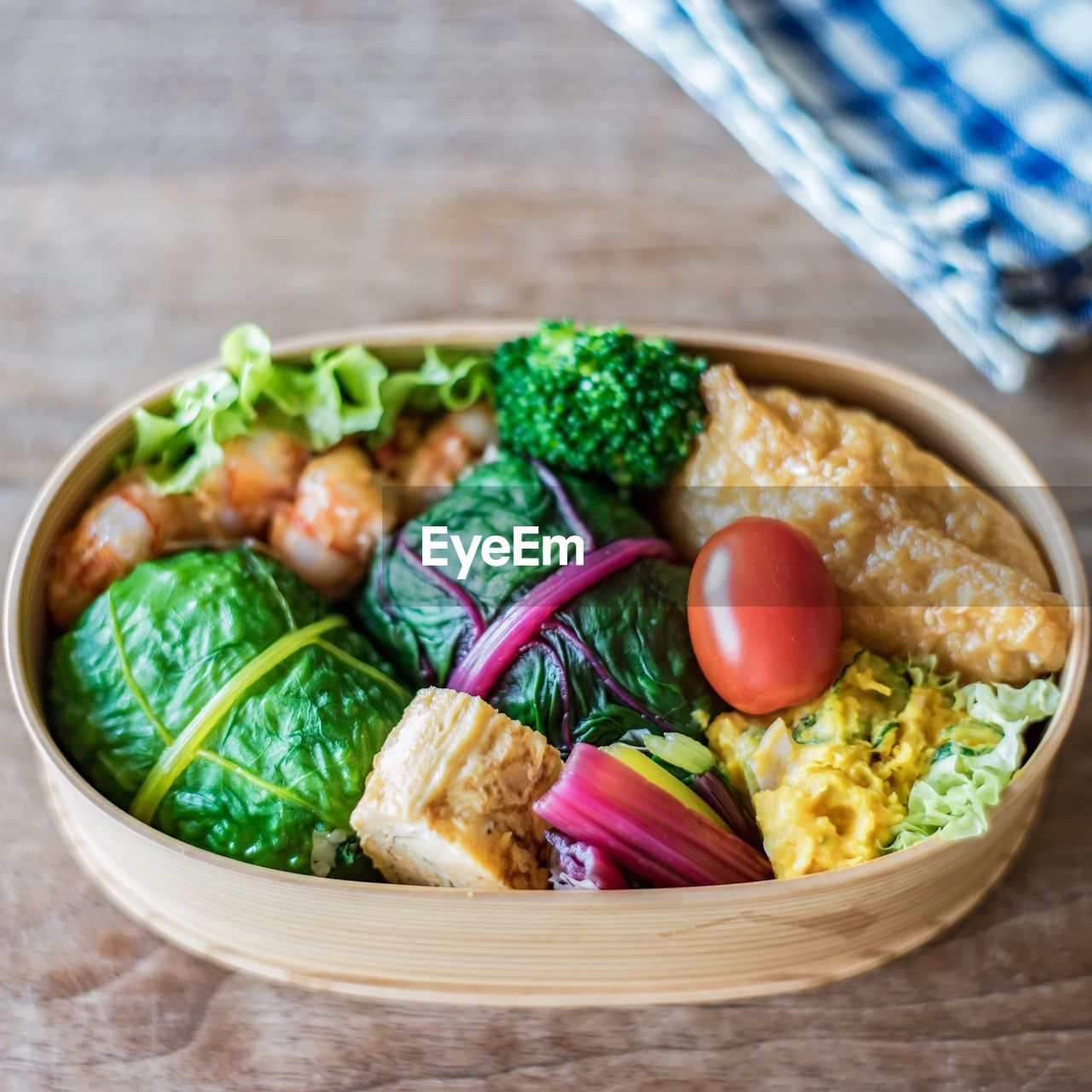 Close-up of wooden container with variety of vegetables and seafood