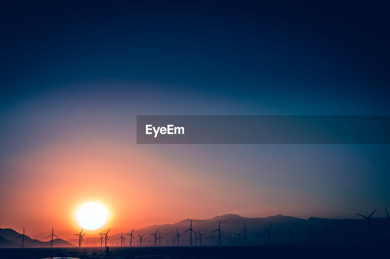 Scenic view of silhouette mountains and windmills against sky during sunset