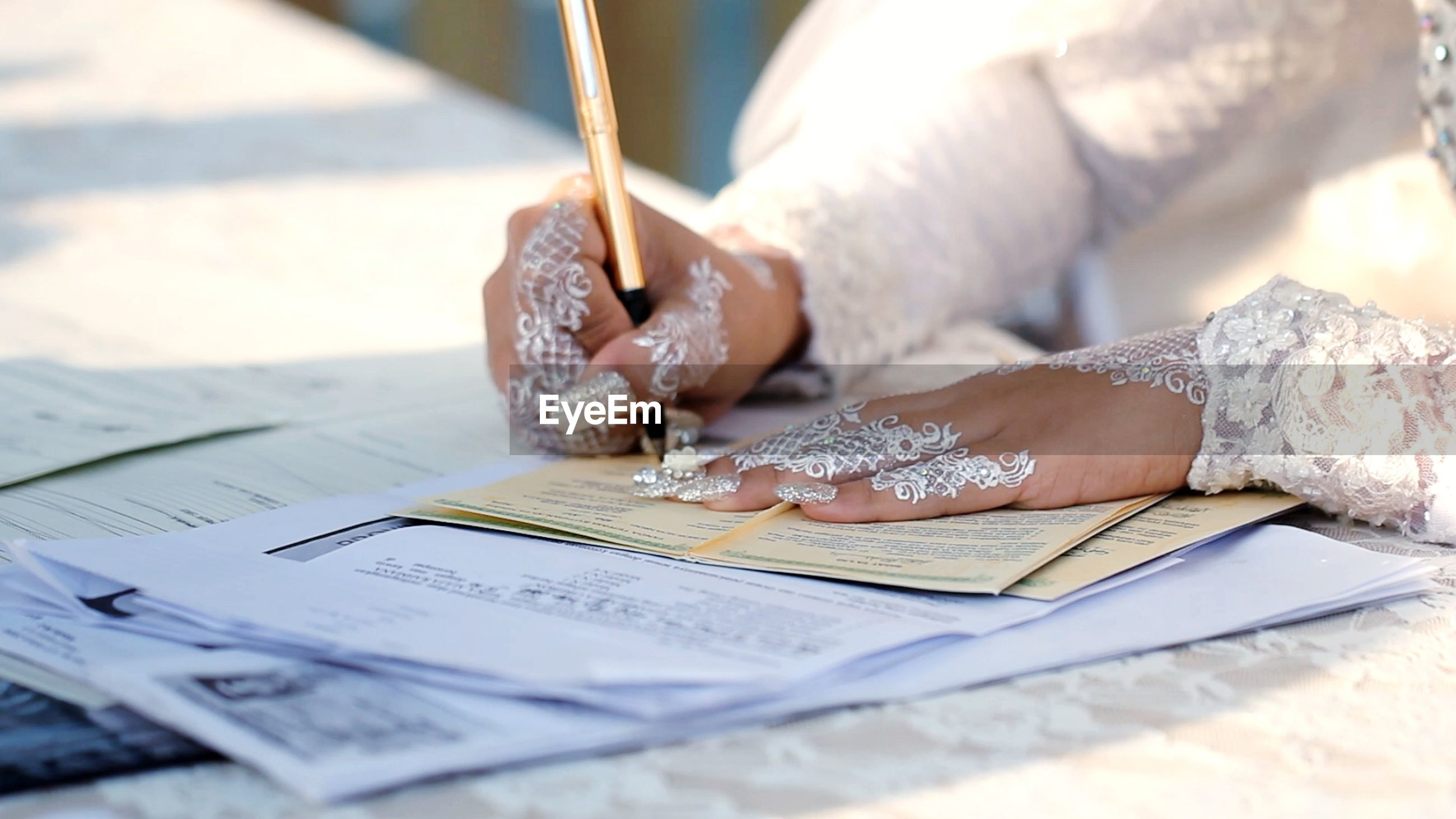 Close-up of bride writing on table