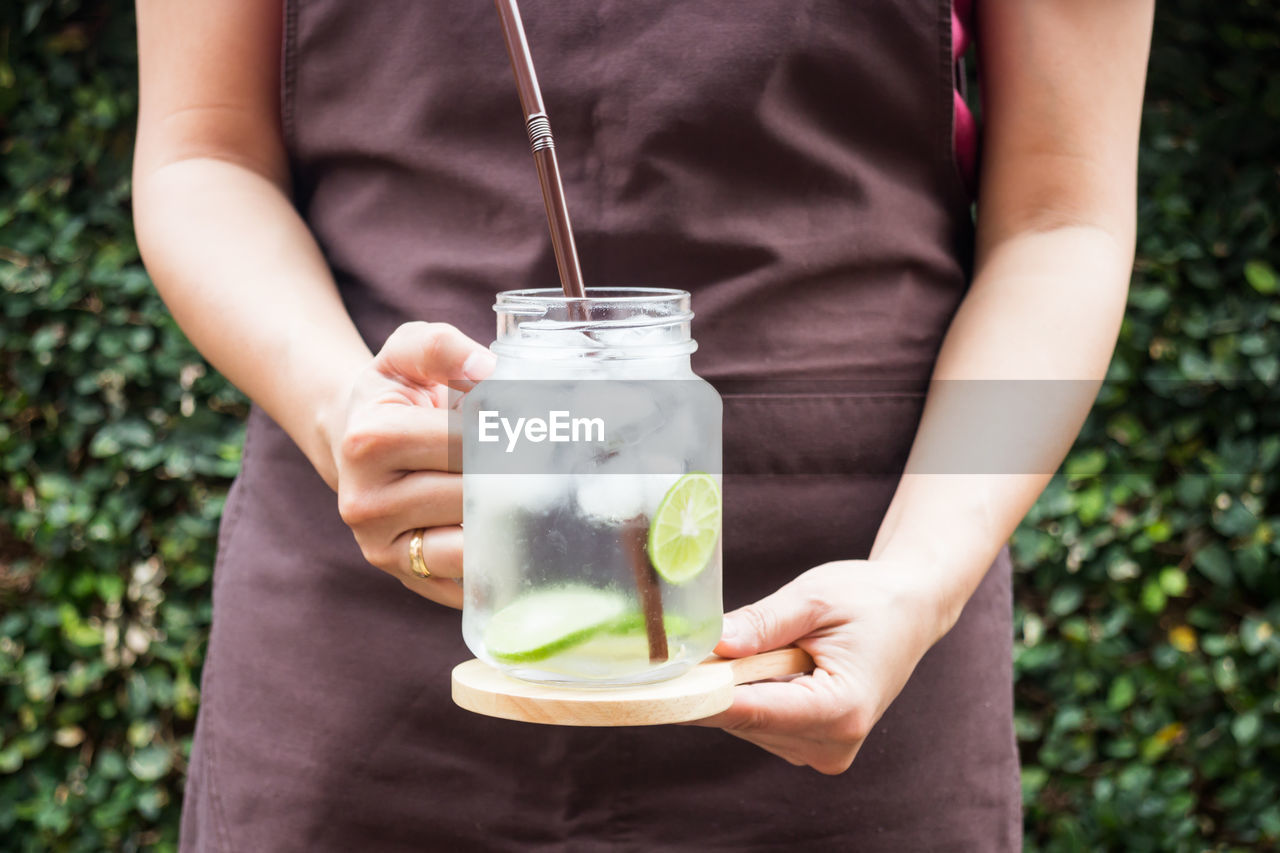 midsection, holding, food and drink, one person, real people, front view, freshness, refreshment, focus on foreground, lifestyles, human hand, food, drink, day, healthy eating, straw, women, drinking straw, wellbeing, hand, glass, outdoors, herb, cocktail, mint leaf - culinary