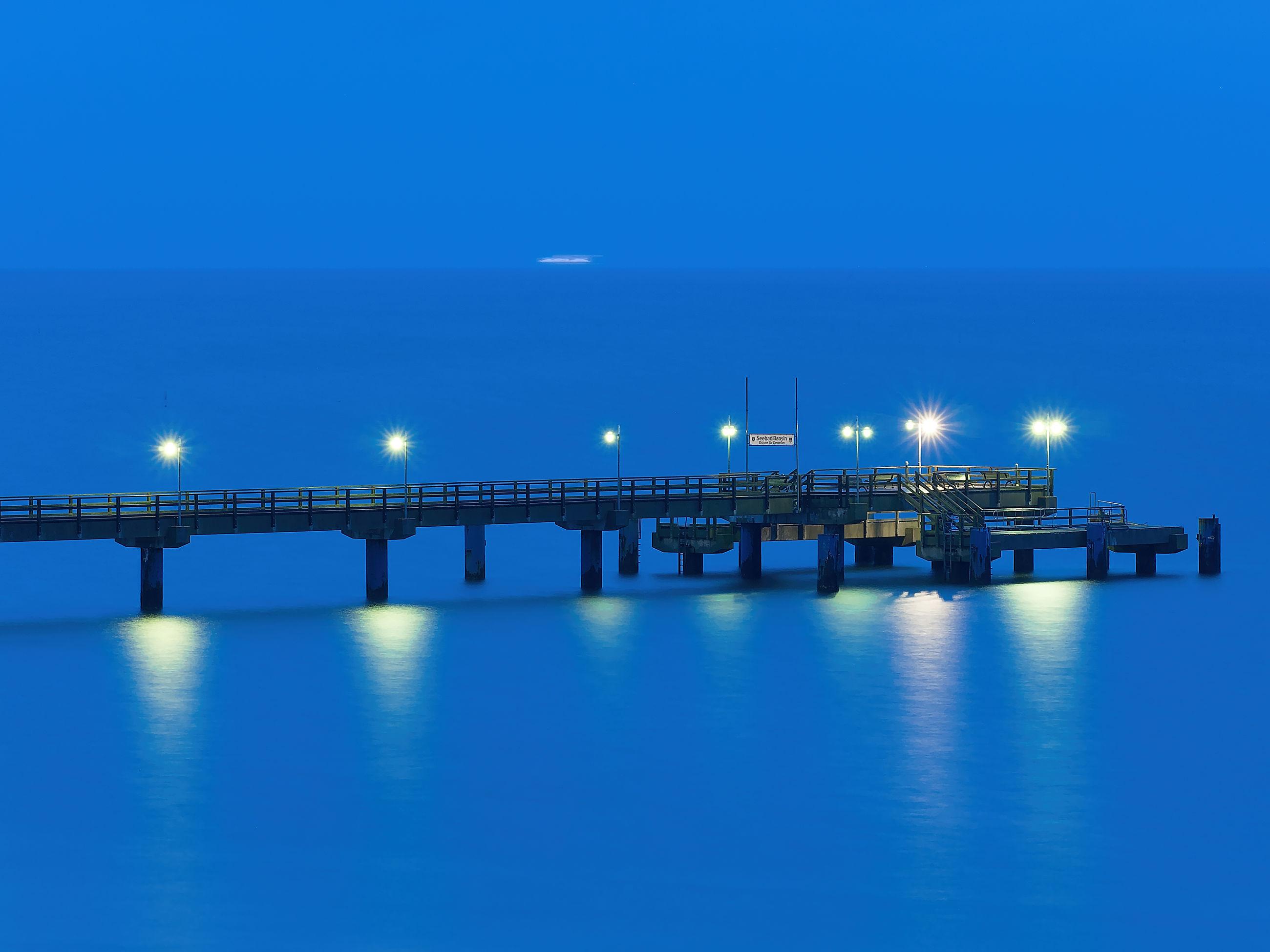 ILLUMINATED BRIDGE OVER SEA AGAINST BLUE SKY