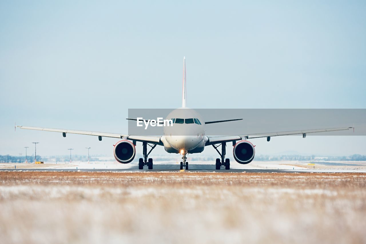 Airplane On Airport Runway Against Clear Blue Sky