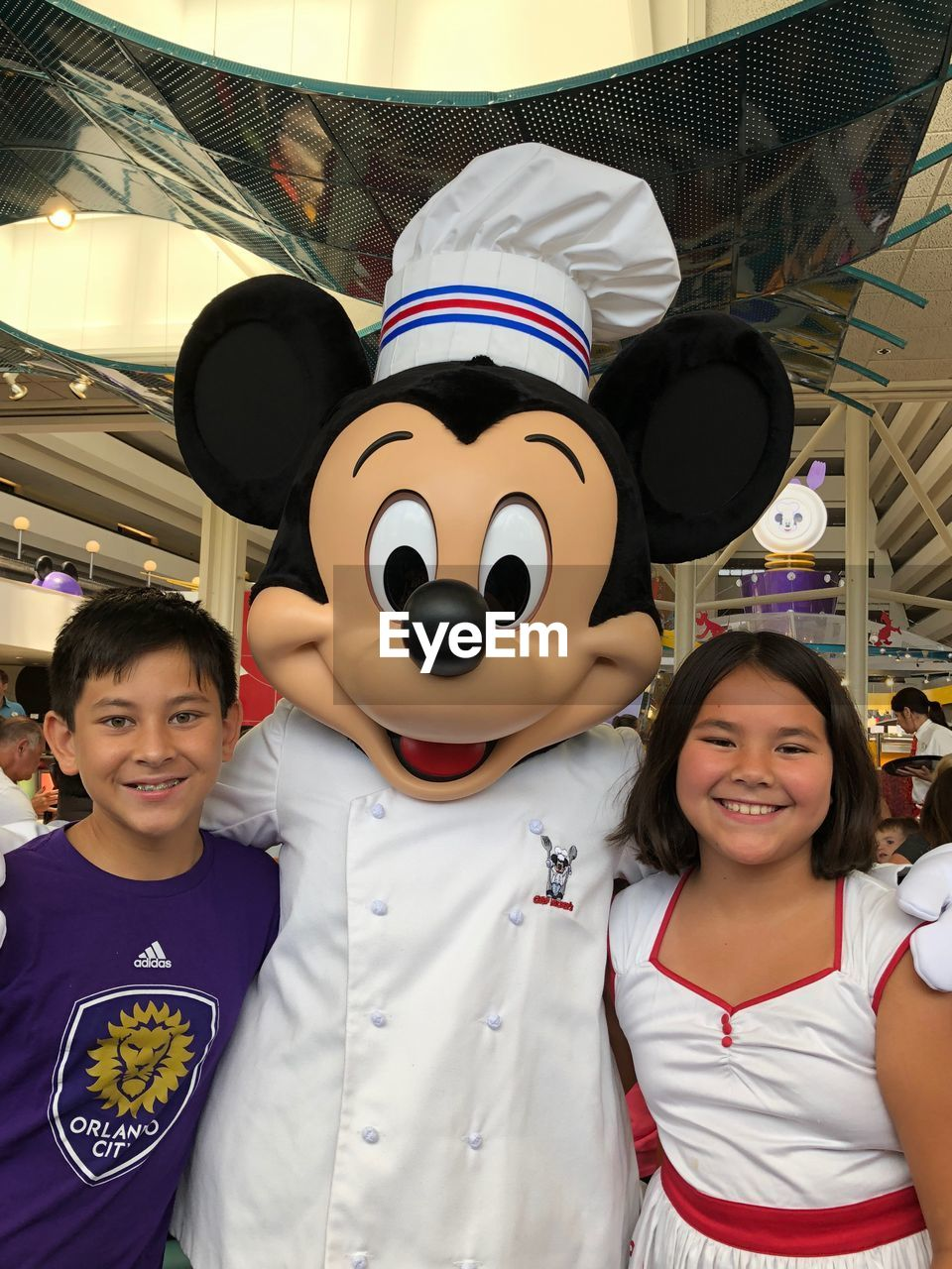 Portrait of smiling siblings with mickey mouse standing in shopping mall
