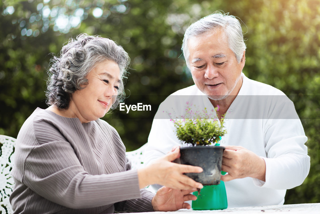 senior adult, senior women, two people, togetherness, emotion, women, adult, smiling, holding, plant, leisure activity, casual clothing, lifestyles, happiness, day, flowering plant, people, front view, flower, positive emotion, couple - relationship, outdoors, white hair, hairstyle