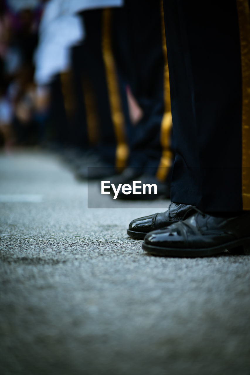 low section, shoe, human leg, selective focus, human body part, real people, body part, people, standing, lifestyles, unrecognizable person, limb, men, street, human foot, flooring, indoors, city, human limb, surface level