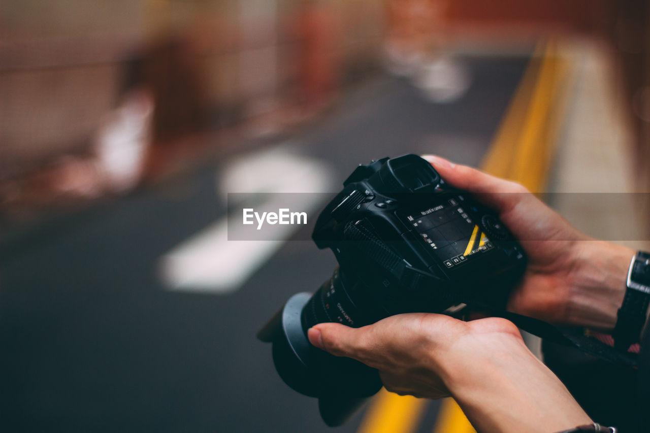 Cropped image of hands holding digital camera